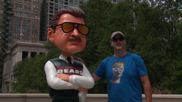 vídeos de stock e filmes b-roll de wgn chicago il us two men posing with a new 7foot high bobblehead of chicago bears' super bowlwinning coach mike ditka in millennium park on friday... - boné de basebol