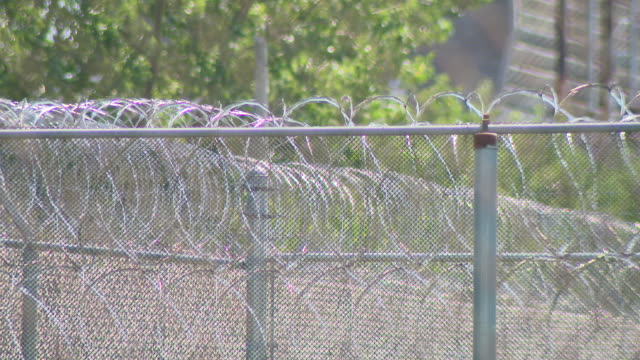 chicago, il, u.s. - warning sign and barbed wired fences of prison. keith walker was in his twenties when he was sentenced to life in prison, after... - mensch und maschine stock-videos und b-roll-filmmaterial