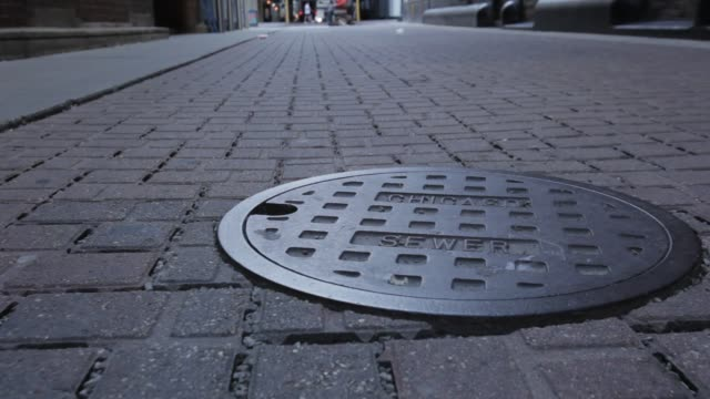 vídeos y material grabado en eventos de stock de chicago illinois sewer manhole cover, permeable material and traffic in background. - tapadera de cloaca