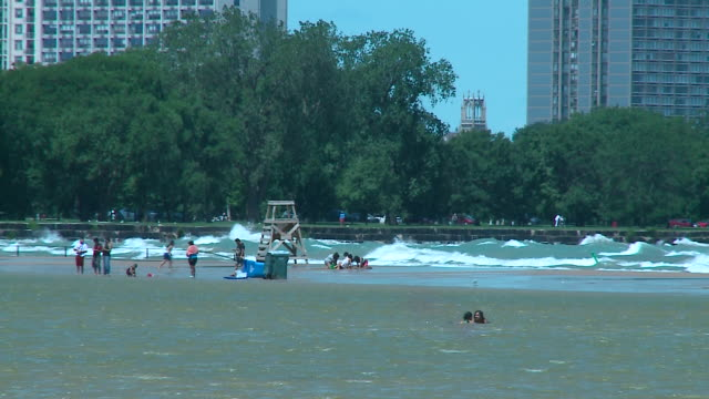 wgn chicago illinois us people at chicago beach as dangerous high waves crash on monday july 27 2019 - lake michigan stock videos & royalty-free footage