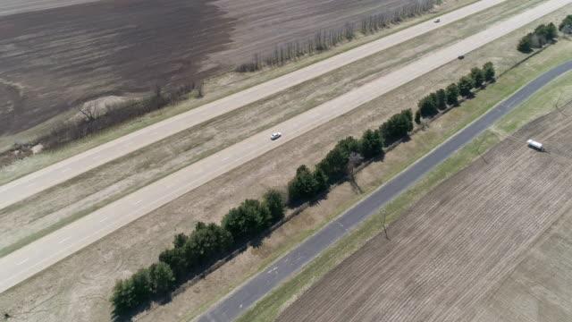 vídeos de stock, filmes e b-roll de chicago-kansas city expressway cercado pelos campos agriculturais na primavera, próximo township de lyndon, illinois, eua. vídeo drone aéreo cinematográfico com o movimento da câmera para frente. - chicago illinois