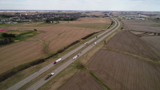chicago - kansas city expressway surrounded by the agricultural fields in the springtime, nearby lyndon township, illinois, usa. cinematic aerial drone video with the wide panoramic-orbit camera motion. - illinois stock videos & royalty-free footage