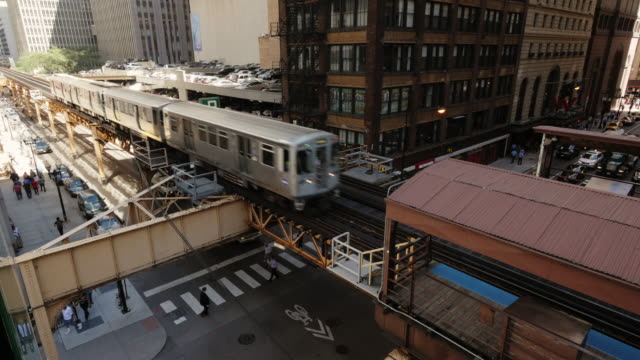 chicago l train arriving in station on elevated track. view from above - chicago 'l' stock videos & royalty-free footage
