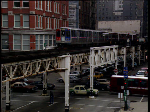 chicago l (elevated) train passes through inner city as traffic moves slowly below; chicago - chicago 'l' stock videos & royalty-free footage
