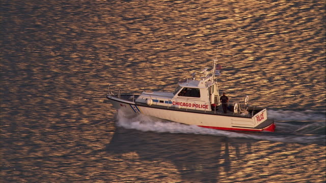 a chicago police boat speeds across the water. - police boat stock videos and b-roll footage