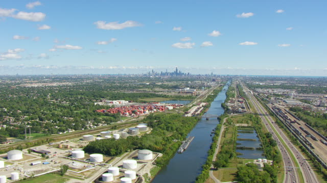 ws aerial pov chicago river passing through industrial building and railroad yard, downtown in background / chicago, cook county, illinois, united states - industrial district stock videos & royalty-free footage
