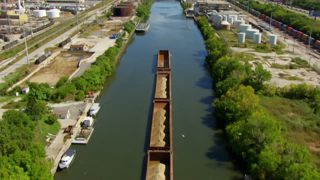 ws aerial pov chicago river passing through industrial building and railroad yard, downtown in background / chicago, cook county, illinois, united states - barge stock videos & royalty-free footage