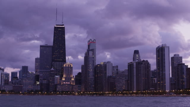 vídeos de stock, filmes e b-roll de t/l ws chicago skyline across lake michigan against cloudy sky, day to dusk / chicago, illinois, usa - 2009