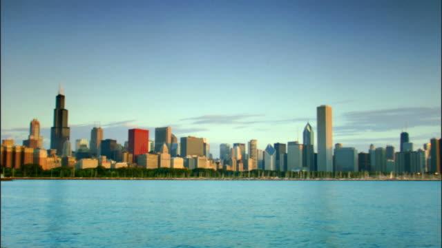 vídeos de stock, filmes e b-roll de t/l, ws, chicago skyline across lake michigan, illinois, usa - chicago 'l'