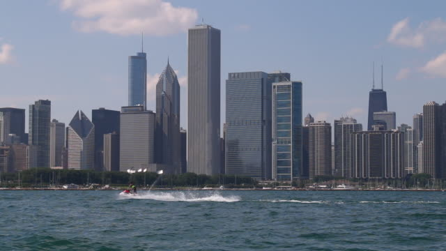 ws chicago skyline, jet skis passing - lago michigan video stock e b–roll