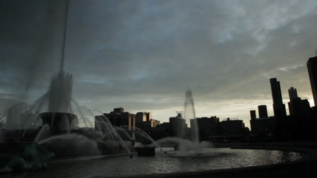 chicago's buckingham fountain at dusk with silhouettes of skyline - buckingham fountain stock videos & royalty-free footage