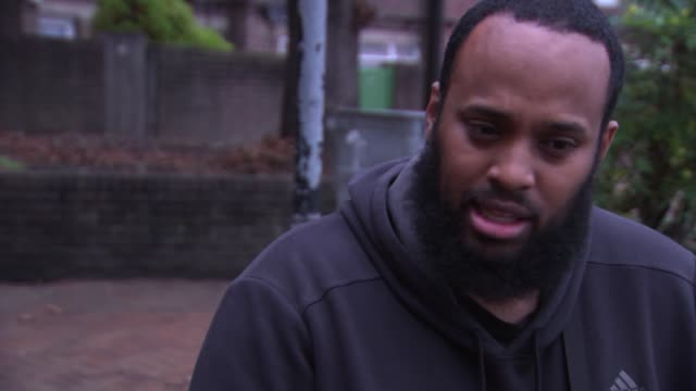 chicago's cure violence team bring their message to london; england: london: lambeth: ext mikey davis along through council estate as talking to... - lambeth stock videos & royalty-free footage