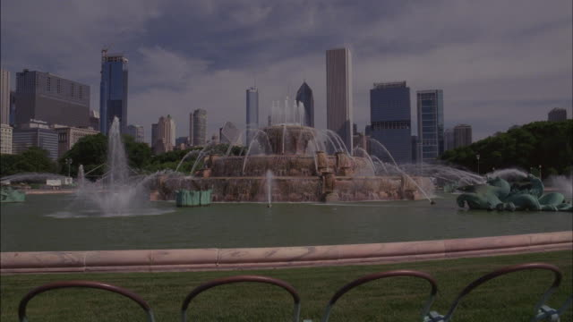 chicago's skyline rises beyond buckingham fountain. - buckingham fountain stock videos & royalty-free footage