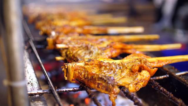 griglia di pollo su stufa calda, cibo di strada - coscia gamba umana video stock e b–roll