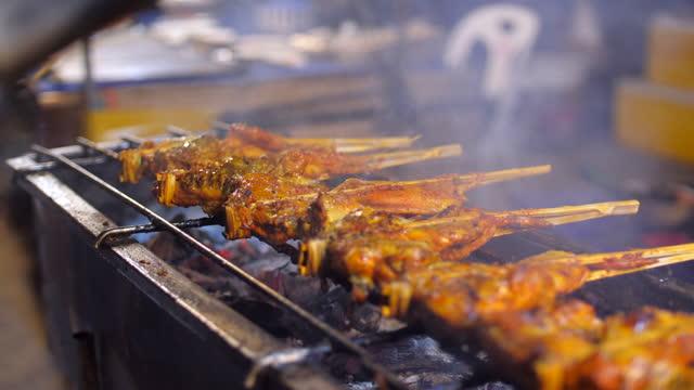 griglia di pollo che ruota su stufa calda, cibo di strada, thailandia - coscia gamba umana video stock e b–roll