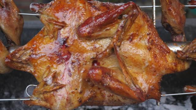 griglia di pollo che ruota su stufa calda, cibo di strada - coscia gamba umana video stock e b–roll