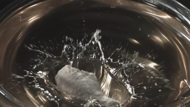 Chicken leg impacting cooking oil.