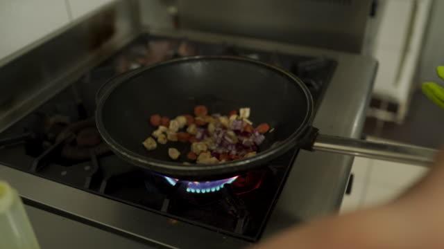 vídeos de stock, filmes e b-roll de carne de frango e legumes fritando em frigideira em um fogão - crocante