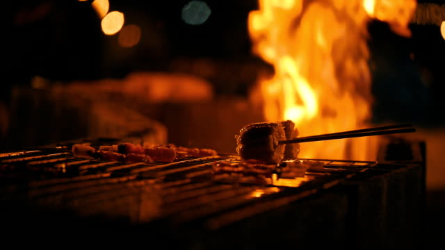 Chicken skewers on grill, BBQ, A group spending time at campfire making barbecue