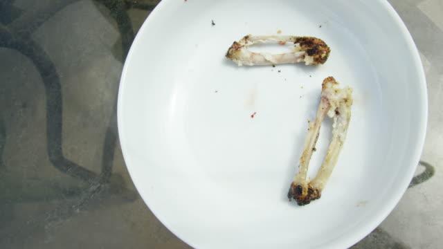 vídeos de stock, filmes e b-roll de ossos da asa de galinha caem sobre uma placa após ser despojado de sua carne - osso