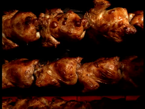 Chickens cook on spinning spits in an oven.