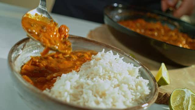 ご飯に加えられるひよこ豆カレー - カレー料理点の映像素材/bロール