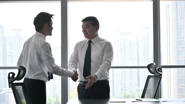 stockvideo's en b-roll-footage met chief executive schudt handen met jonge zakenman - chinese etniciteit