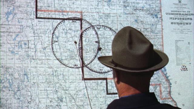 vídeos de stock, filmes e b-roll de ms chief forest ranger pin points fire on wall map / canada  - cartografia