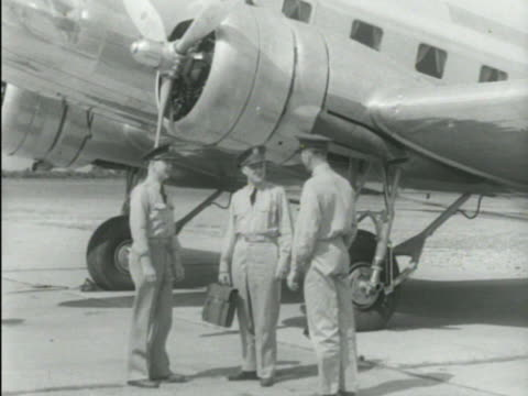 chief general delos emmons standing on tarmac talking w/ other officers w/ boeing model 299 parked bg ha ms army air corps insignia in aircraft... - ボーイング点の映像素材/bロール
