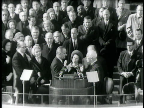 Chief Justice Earl Warren gives the oath of office to President Lyndon B Johnson on January 20 1965