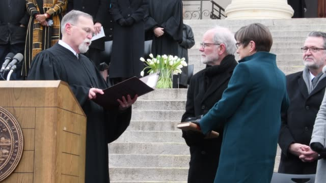 chief justice of the kansas supreme court lawton nuss delivers the oath of office to laura kelly as her husband ted daughrty holds the bible - 長点の映像素材/bロール