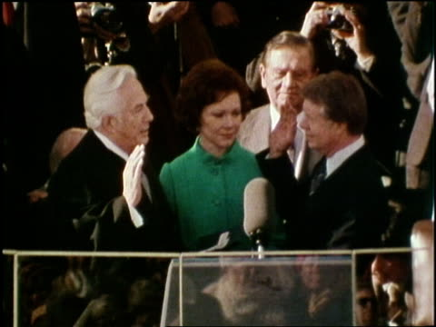 vídeos de stock, filmes e b-roll de chief justice warren e burger gives the oath of office to newly elected president jimmy carter during inauguration ceremonies on january 20 as first... - tomada de posse