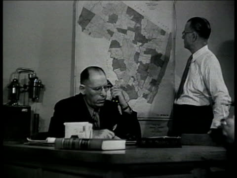 chief mckie at desk picking up telephone man at desk map bg picking up phone coast guard officer at desk answering phone la ws airplane flying over... - 警察署長点の映像素材/bロール