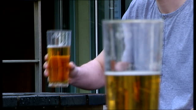 chief medical officer calls for minimum alcohol price to curb binge drinking; england: london: ext people sitting drinking at tables outside bar pint... - lager stock videos & royalty-free footage