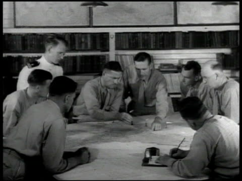 chief of naval operations sign. men in suits in office looking at world wall map. us officers looking at map on table. guam: vehicle driving onto... - 1939 stock-videos und b-roll-filmmaterial