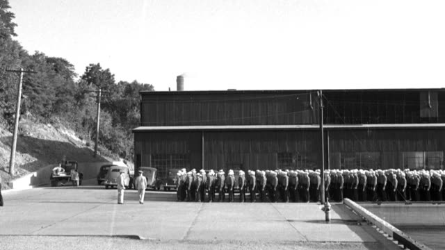 chief petty officers lead a formation of naval recruits as they march away from a naval training center building. - military recruit stock videos & royalty-free footage