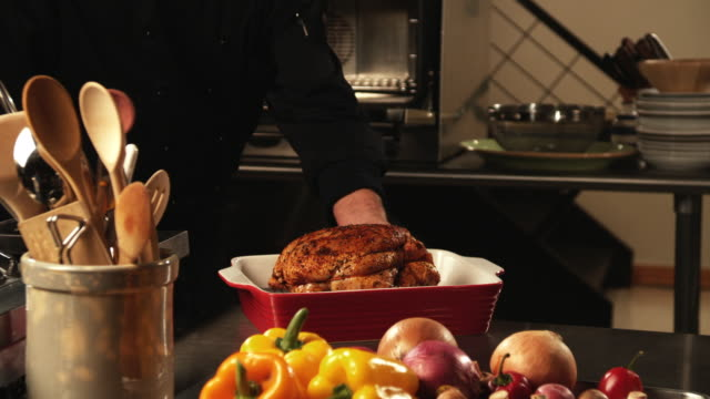 cu, chief placing chicken in oven, mid section - roast chicken stock videos & royalty-free footage