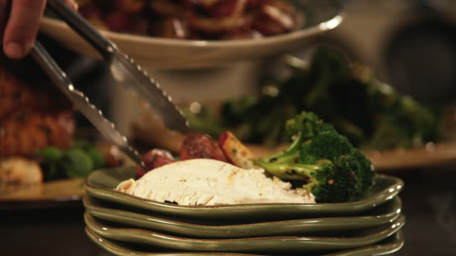vidéos et rushes de cu, tu, td, chief's hands placing roasted potatoes beside broccoli and slice of chicken on plate - pomme de terre rouge
