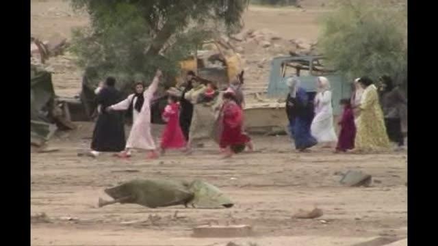 stockvideo's en b-roll-footage met continued unrest in iraq t09110450 / tx iraq fallujah ext iraqi women and children fleeing attack past rubble - al fallujah