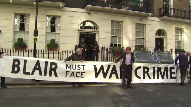 protests at Tony Blair's house ENGLAND London EXT Police on doorstep / Protesters outside Tony Blair's house unfurl large banner reading 'Blair must...