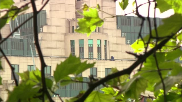 chilcot report to be published: examining britain's biggest intelligence failure in decades; london: mi6 building seen through tree branches and... - mi6点の映像素材/bロール