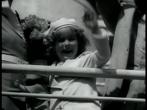 Child actor Shirley Temple in coat hat standing behind railing on ship smiling waving SALLY RAND Sally in suit standing holding fan smiling putting...