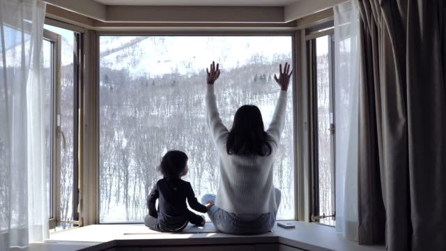 vídeos de stock e filmes b-roll de a child and his mother sitting near a window and watching snow falling in forest.. - olhar através da janela