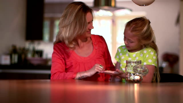 Child and mother saving money in piggy bank