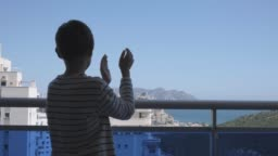Child applauding medical staff from their balcony. People in Spain clapping gratitude on balconies and windows in support of health workers, doctors and nurses during the Coronavirus pandemic