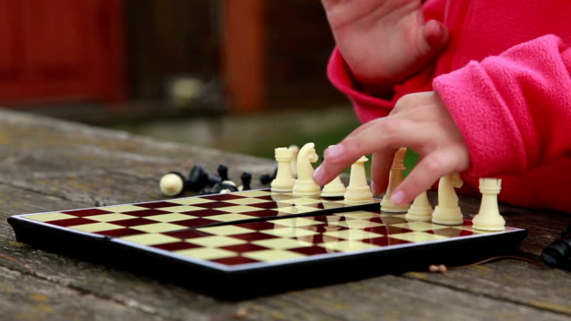 child arranging white chess pieces on the chessboard in the backyard - patriarchy stock videos & royalty-free footage