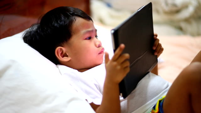 Child at home using digital tablet