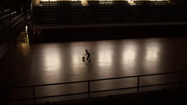 A boy practices dribbling a basketball alone in a gym.