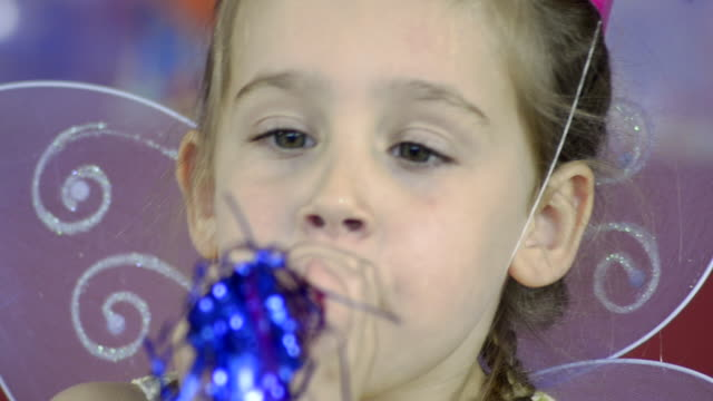 A child Blows into a Noisemaker at a Birthday Party