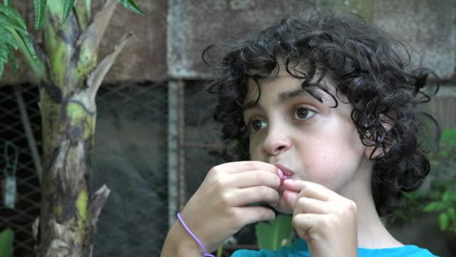 child boy eating a sour fruit on a backyard, cuba - sour taste stock videos & royalty-free footage